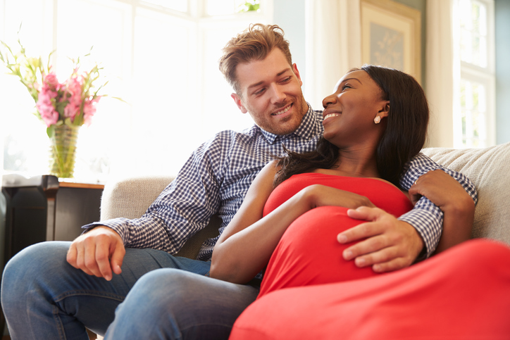 Pregnant Couple At Home Relaxing On Sofa Together