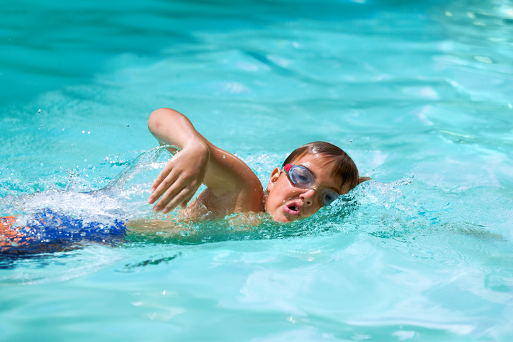 Close up of young boy at swimming practice outdoors.