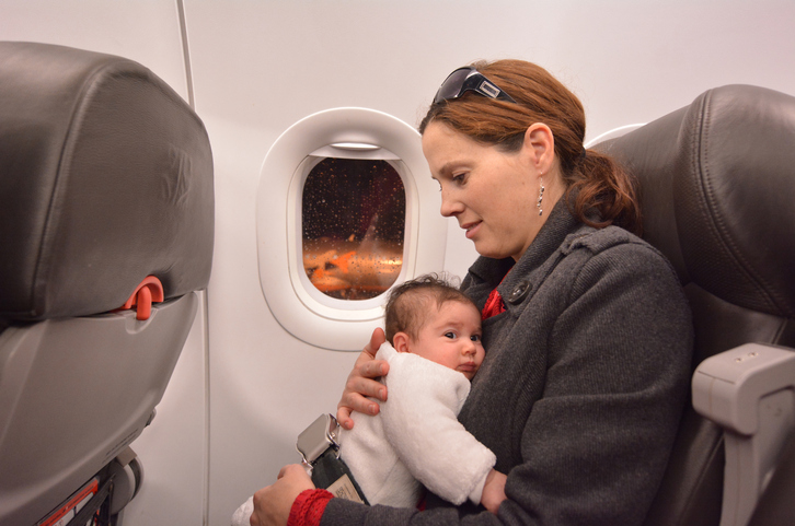 Mother carries her newborn baby during flight.Concept photo of air travel with baby.