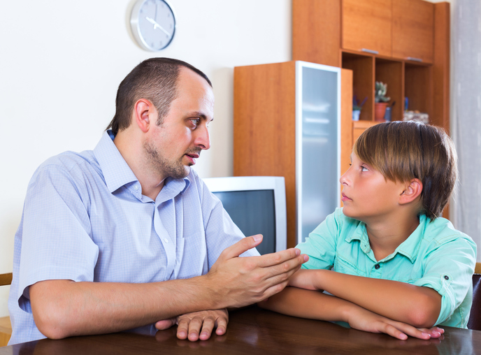 Father and son discussing something serious in living room